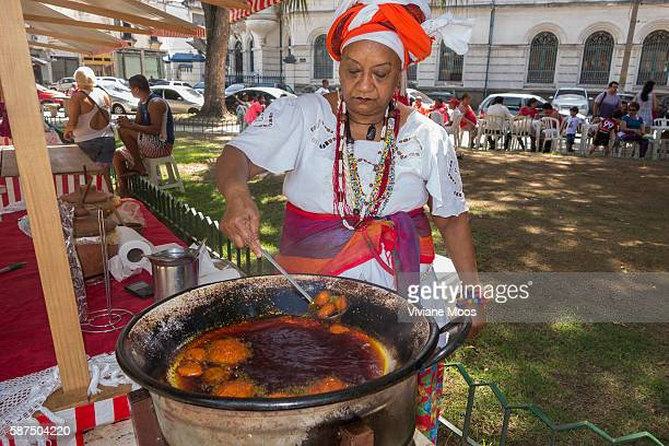 Saint George day pageantry and procession Big Bayana woman from Bahia on her traditional dress serving her traditional deep fried acaraje fritters