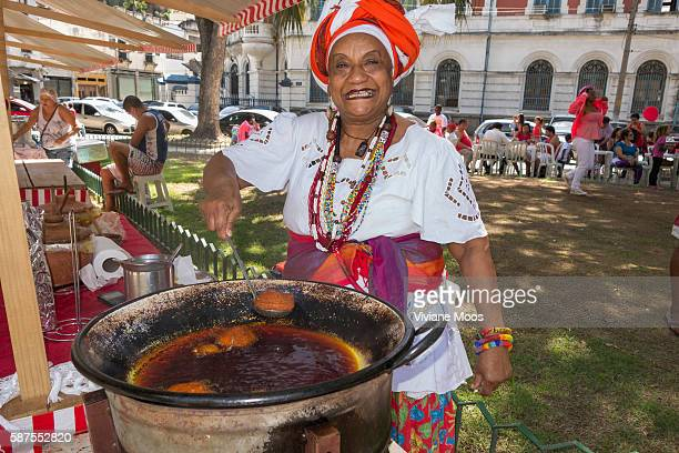 Saint George day pageantry and procession Sonia a big Bayana woman from Bahia in her traditional dress preparing her traditional deep fried acaraje...