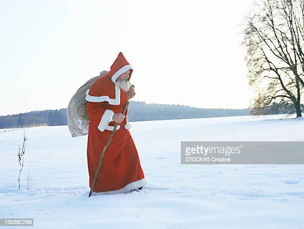 Saint Nicholas walking through winter landscape