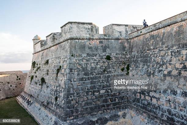 Saint Peter of the Rock castle Man sitting on top of a fortified stone wall with a cloudy blue sky scenic background El Morro de Santiago de Cuba is...