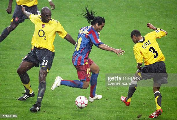 Barcelona's Brazilian forward Ronaldinho vies with Arsenal's English defender Ashley Cole and Arsenal's English defender Sol Campbell during the UEFA...