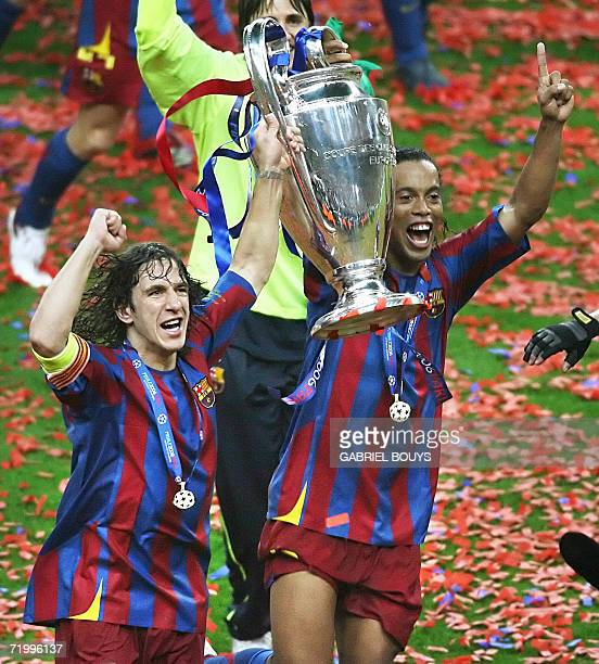Barcelona's Spanish defender and team captain Carles Puyol and his Brazilian teammate Ronaldinho celebrate with the trophy after winning the UEFA...