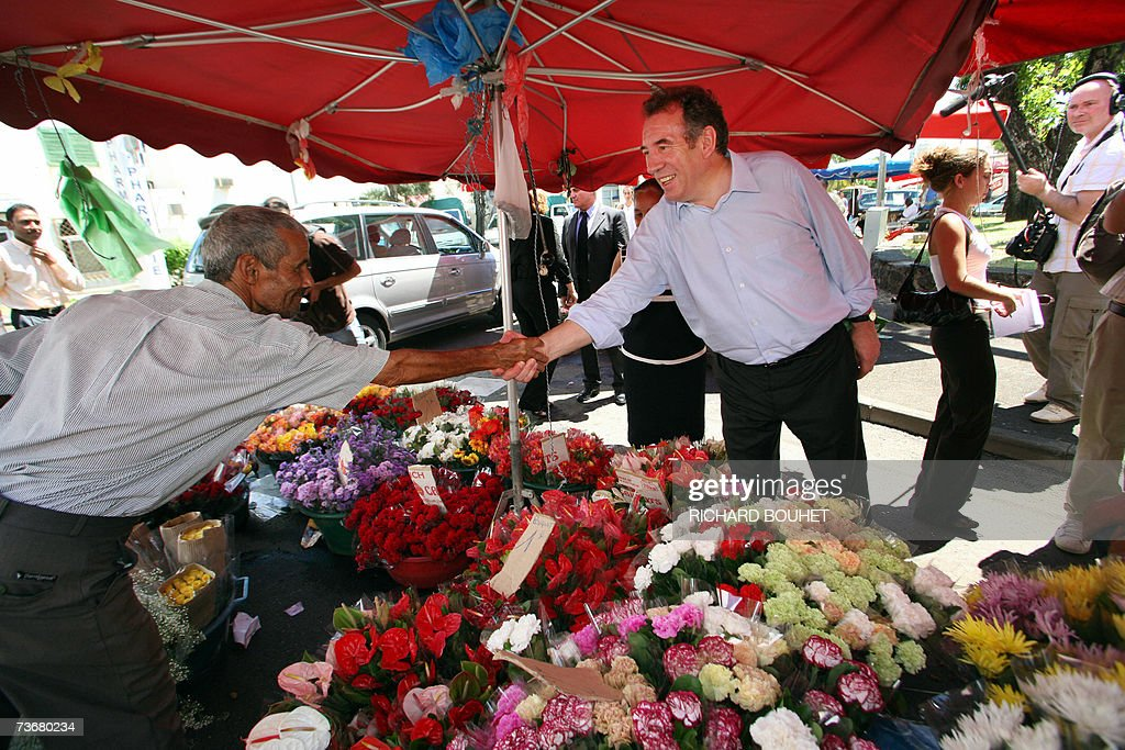 Union for the French Democracy (UDF) centrist party President and presidential candidate Francois Bayrou (C) visits the Camelias market in Saint-Denis-de-la-Reunion, on the French Indian Ocean Island of La Reunion, 23 March 2007. Francois Bayrou, the centrist who has emerged as a serious contender in France's presidential race, showed the first sign of losing ground yesterday as an opinion poll put him down four points in first round voting intentions. AFP PHOTO RICHARD BOUHET