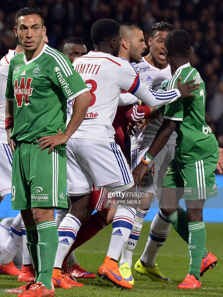 Saint-Etienne French forward Mevlut Erding (L) looks on while Lyon's and Saint-Etienne's players clash during the French L1 football match between Lyon and Saint-Etienne on April 19, 2015 at the Gerland stadium in Lyon. AFP PHOTO / PHILIPPE MERLE
