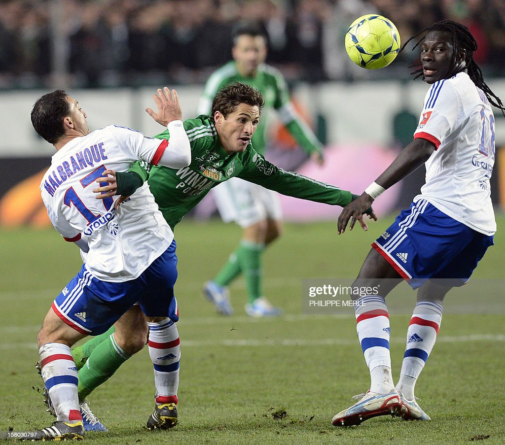Saint-Etienne midfielder Jeremy Clement (C) fights for the ball with Lyon's Belgian midfielder Steed Malbranque (L) on December 9, 2012 during a French L1 football match at the Geoffroy-Guichard stadium in the central city of Saint-Etienne. MERLE