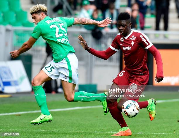 SaintEtienne's French defender Kevin Malcuit vies with Metz's Senegalese midfielder Ismaila Sarr during the French L1 football match SaintEtienne vs...