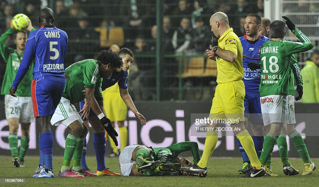Saint-Etienne's French midfielder Jeremy Clement (C) lies on the pitch after being hurt during the French L1 football match Saint-Etienne vs Nice, on March 2, 2013 at the Geoffroy Guichard stadium in Saint Etienne. AFP PHOTO THIERRY ZOCCOLAN