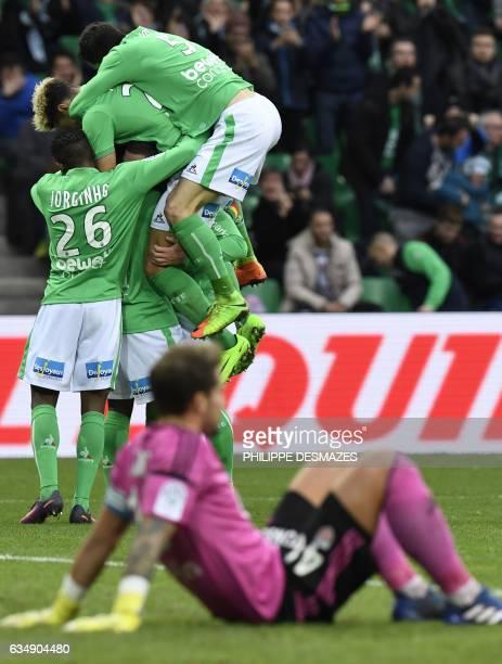 SaintEtienne's French midfielder Jordan Veretout celebrates with teammates after scoring a goal as Lorient's French goalkeeper Benjamin Lecomte lies...