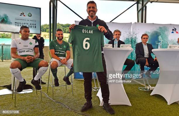SaintEtienne's Spanish head coach Oscar Garcia poses with the new jersey of the Ligue 1 football team at a press conference in L'Etrat near...