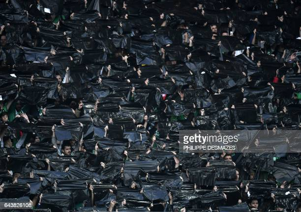 TOPSHOT SaintEtienne's supporters hold black plastic bags during the UEFA Europa League football match between AS SaintEtienne and Manchester United...