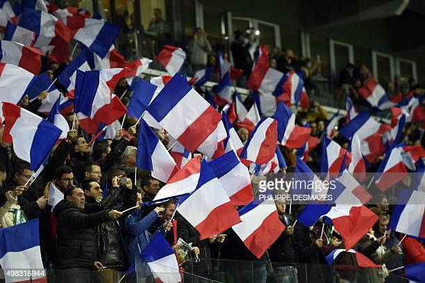 SaintEtienne's supporters hold French national flags in tribute to the victims of Paris attacks prior to the French Ligue 1 football match between AS...