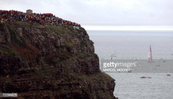 People are gathered to watch sailing boats crosse the Frehel Cape after the start of the solo sailing race 'Route du Rhum Banque Postale' from...