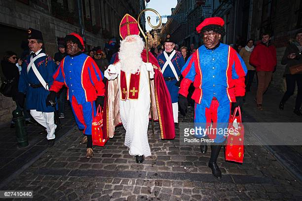 SaintNicholas and his two helpers dressed traditionally as Black Pete characters walk through Brussels on the annual SaintNicholas parade