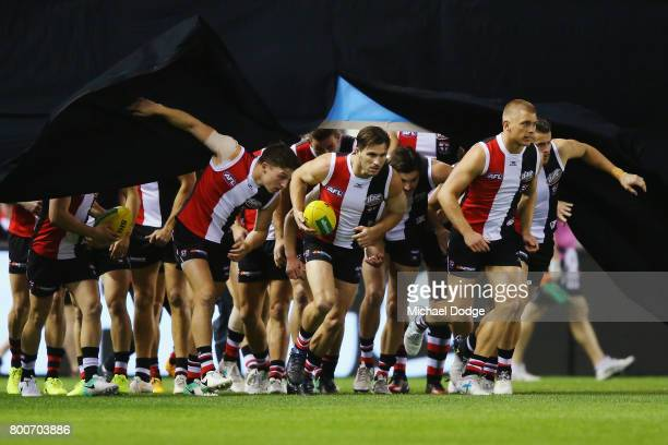 Saints players run through their banner during the round 14 AFL match between the St Kilda Saints and the Gold Coast Suns at Etihad Stadium on June...