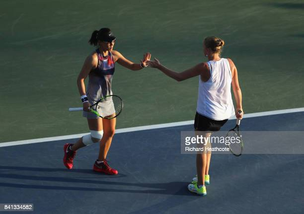Saisai Zheng of China and Alla Kudryavtseva of Russia react against Taylor Johnson and Claire Liu of the United States during their first round Wom...
