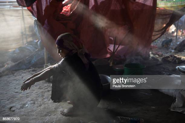Sajida Begum sits in her makeshift tent washing rice for dinner as smoke catches the late afternoon light September 25 2017 in Thainkhali camp Cox's...