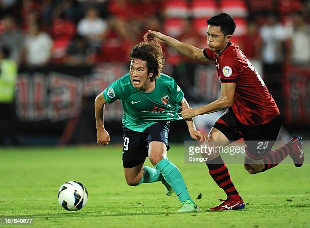 Sakano Toyofumi of Urawa Red Diamonds and Piyaporn Buntao of Muangthong United Diamonds fight for the ball during the AFC Champions League match...