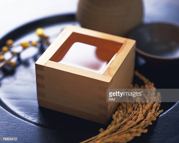 Sake in square wooden box and rice plants, high angle view, differential focus