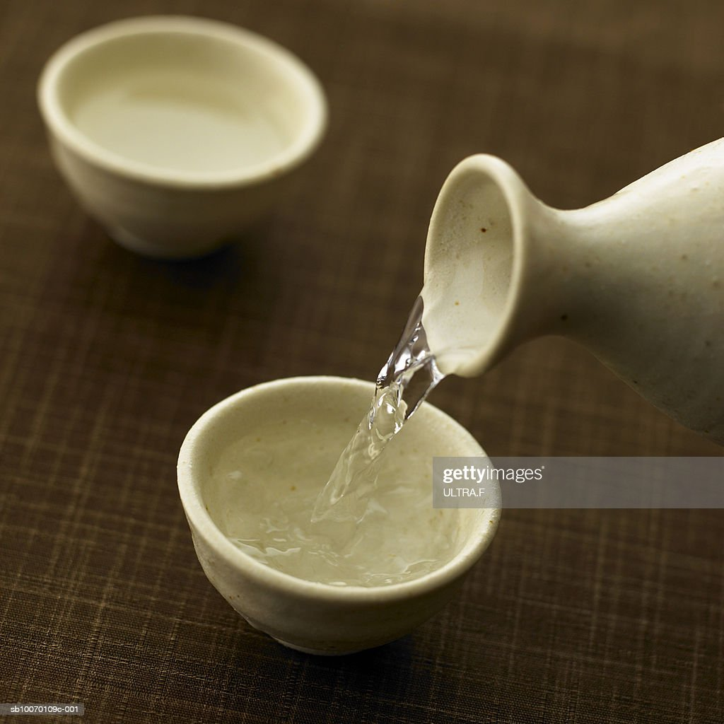 Sake is poured into sake cup, studio shot