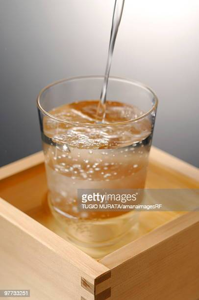 Sake pouring into glass, colored background