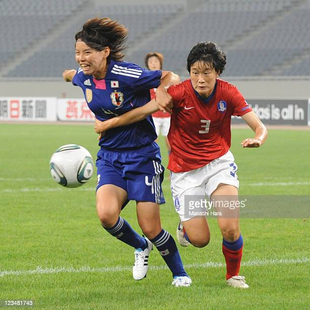 Saki Kumagai of Japan and Lee Eum Mi of South Korea compete for the ball during the London Olympic Women's Football Asian Qualifier match between...
