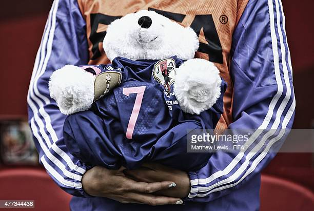 Saki Kumagai of Japan holds a bear wearing a shirt in honour of Kozue Ando after she broke her leg in an earlier match ahead of the FIFA Women's...
