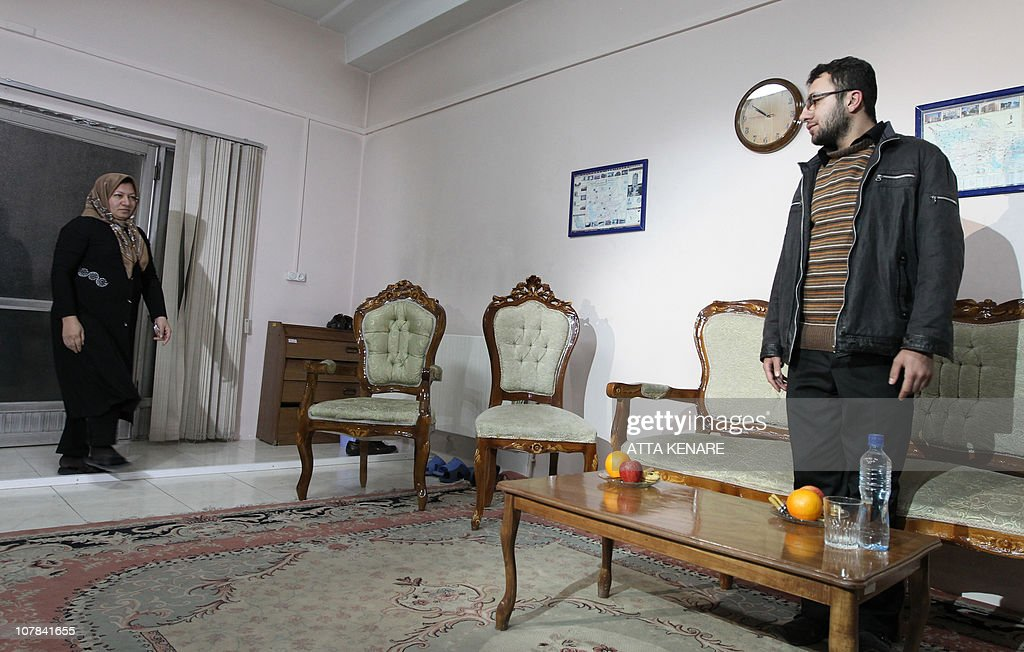 Sakineh Mohammadi Ashtiani, an Iranian woman sentenced to death by stoning for adultery, walks towards her son Sajjad Qaderzadeh during an interview with a group of journalists from international news networks at a guesthouse belonging to a government welfare organisation in Iran's northwestern city of Tabriz on January 1, 2011. The 43-year-old woman said that she would sue two German journalists who have been jailed in Iran for interviewing her son.