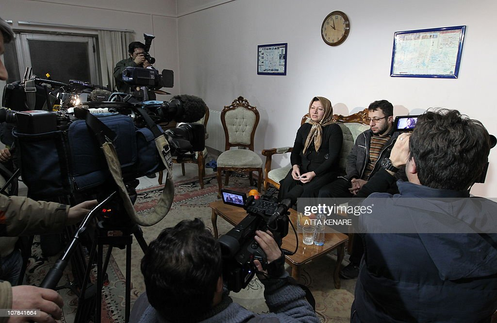 Sakineh Mohammadi Ashtiani, an Iranian woman sentenced to death by stoning for adultery, sits next to her son Sajjad Qaderzadeh during an interview with a group of journalists from international news networks in Iran's northwestern city of Tabriz on January 1, 2011. The 43-year-old woman said that she would sue two German journalists who have been jailed in Iran for interviewing her son. AFP PHOTO/ATTA KENARE