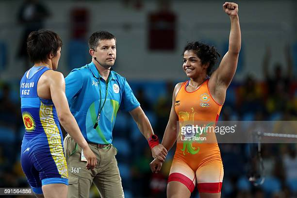 Sakshi Malik of India is declared the winner against Aisuluu Tynybekova of Kyrgyzstan during the Women's Freestyle 58 kg Bronze match on Day 12 of...
