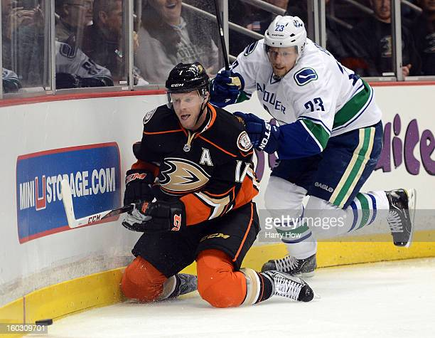 Saku Koivu of the Anaheim Ducks and Alexander Edler of the Vancouver Canucks skate after the puck at Honda Center on January 25 2013 in Anaheim...