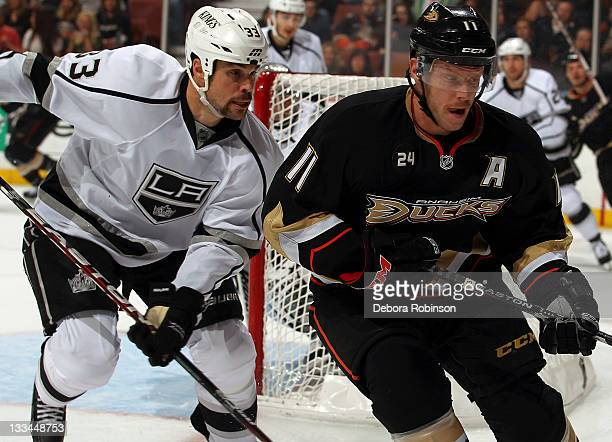 Saku Koivu of the Anaheim Ducks battles against Willie Mitchell of the Los Angeles Kings during the game on November 17 2011 at Honda Center in...