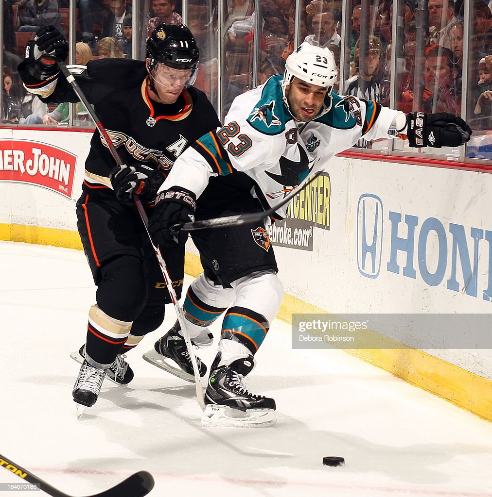Saku Koivu #11 of the Anaheim Ducks battles for the puck against Scott Gomez #23 of the San Jose Sharks on March 18, 2013 at Honda Center in Anaheim, California.