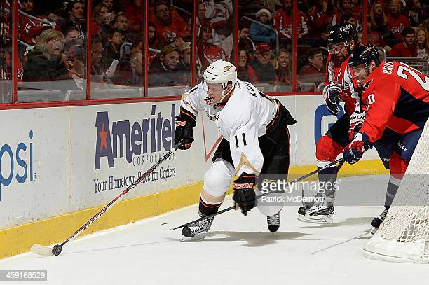 Saku Koivu of the Anaheim Ducks brings the puck around the net against Troy Brouwer of the Washington Capitals in the first period during an NHL game...