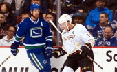 Saku Koivu of the Anaheim Ducks celebrates after scoring a goal as Daniel Sedin of the Vancouver Canucks skates past in the background during the...