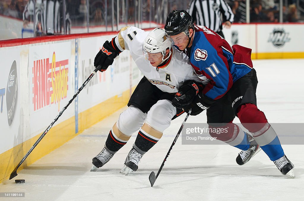 Saku Koivu #11 of the Anaheim Ducks controls the puck while under pressure from Jamie McGinn #11 of the Colorado Avalanche at the Pepsi Center on March 12, 2012 in Denver, Colorado. Koivu is skating in his 1000th NHL game.