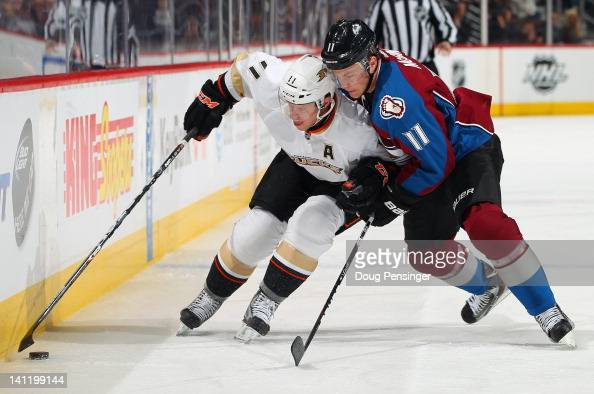 Saku Koivu of the Anaheim Ducks controls the puck while under pressure from Jamie McGinn of the Colorado Avalanche at the Pepsi Center on March 12...