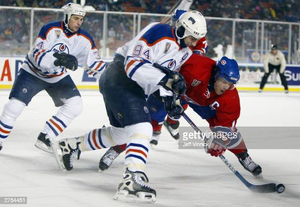Saku Koivu of the Montreal Canadiens and Ryan Smyth of the Edmonton Oilers battle for the puck as Fernando Pisani of the Oilers comes from behind...