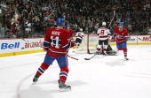 Saku Koivu of the Montreal Canadiens celebrates his goal against Martin Brodeur of the New Jersey Devils as Christopher Higgins of the Canadiens...