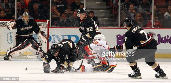 Saku Koivu Toni Lydman and Andrew Cogliano of the Anaheim Ducks battle for the puck against Blair Jones of the Calgary Flames at center ice during...