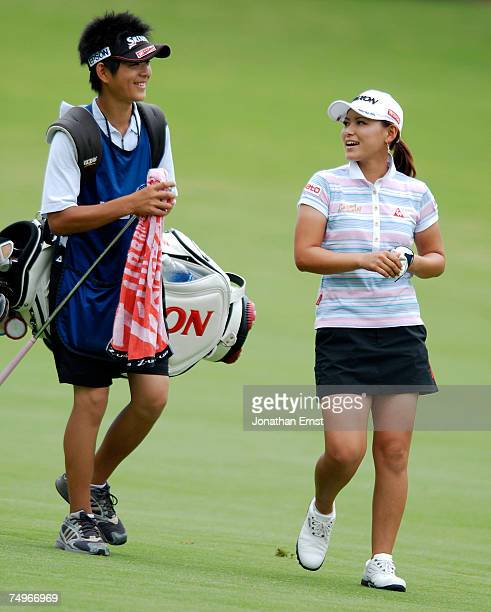 Sakura Yokomine of Japan talks with her caddie Keisuke Arima as the walk up the 18th fairway during the completion of round two of the US Women's...