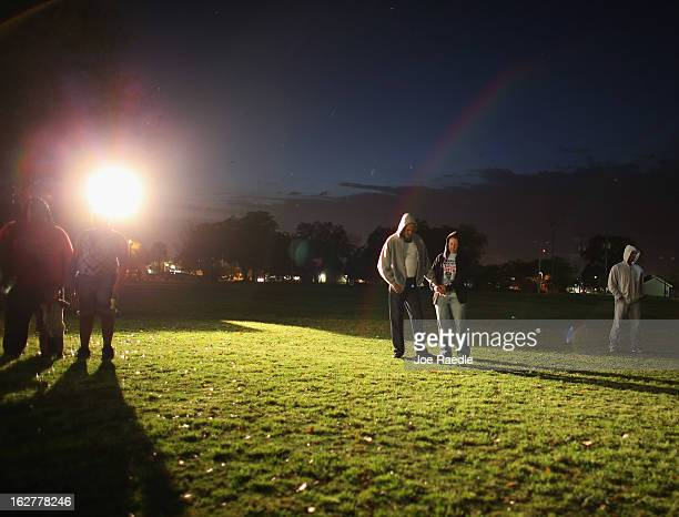 Sal Guardino and Elizabeth Buszta stand together during a prayer before lighting candles during a vigil at Fort Mellon Park to mark the one year...