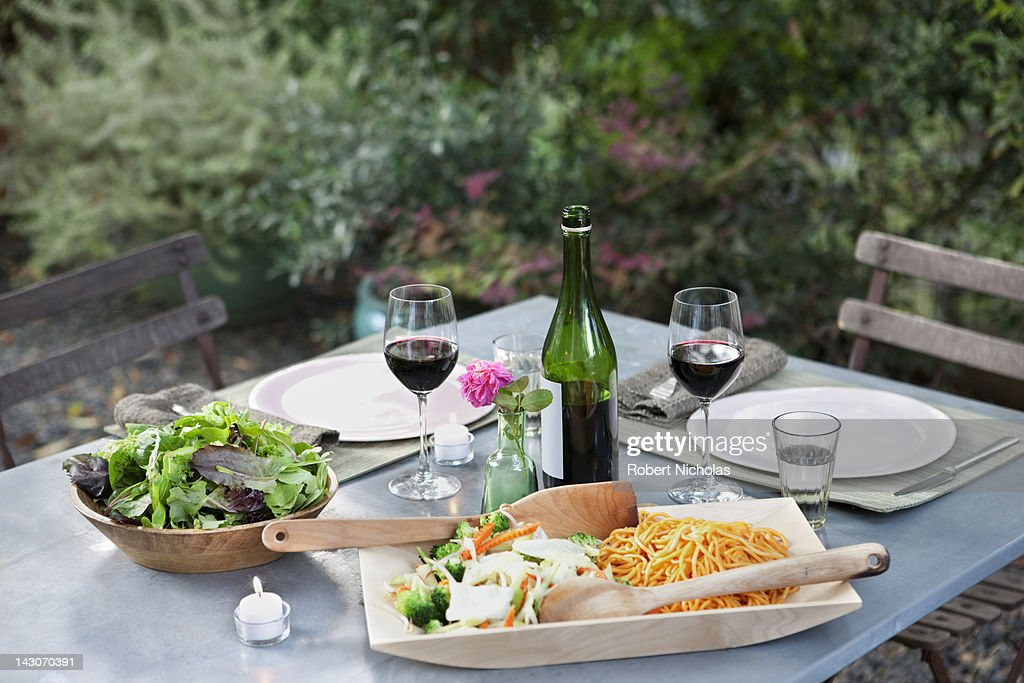 Salad and pasta on set table outdoors : Stock Photo