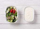 Green salad and yogurt on white table