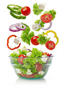 Falling vegetables in a salad bowl, white background
