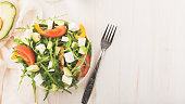 Fresh green arugula, feta cheese, paprika, tomatoes. Bottle of olive oil and glass of water. Diet, healthy eating and weigh loss concept
