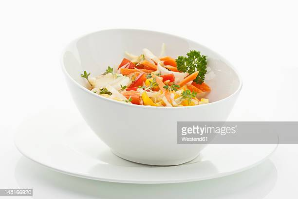 Salad in bowl with plate on white background