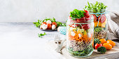 Homemade salad in glass jar with quinoa and vegetables. Healthy food, diet, detox, clean eating and vegetarian concept with copy space.