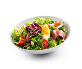 Salad Isolated on White. a bowl of fresh lettuce salad with tomatoes eggs prosciutto over white.