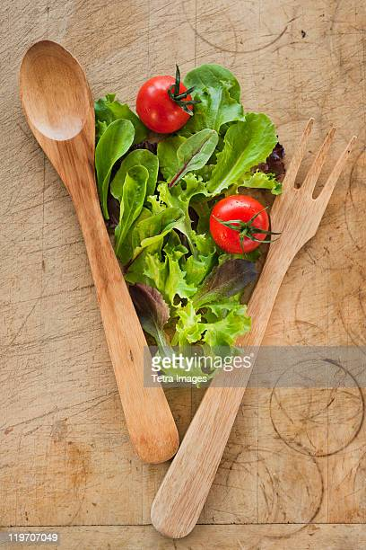 Salad leaves and wooden spoon and fork