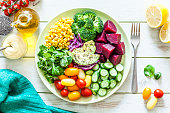 Top view of a blue salad plate filled with fresh organic colorful vegetables shot on light green picnic table. The plate is at the center of an horizontal frame with a fork beside it and is surrounded